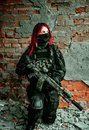 Airsoft Red-hair woman in uniform with machine gun standing on one knee beside brick wall. Soldier nside of broken building Royalty Free Stock Photo