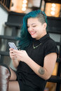 Aisan woman reading text message asian with blue hair sitting and with a smile Royalty Free Stock Photo