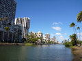 Ala wai canal on oahu hawaii hotels condos and coconut trees a nice day in waikiki Stock Photos