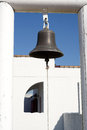 Alarm bell bronze hanging on wooden pillar on a blue sky Stock Photos