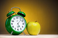 Alarm clock big green with apple on dark yellow background Royalty Free Stock Images