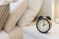 Alarm clock on the nightstad Stock Photography