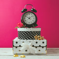 Alarm clock with polka dots boxes over pink modern background glamour feminine objects Stock Photo