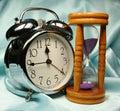 Alarm-clock and sandglass on b