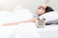 Alarm clock with sick child lying down suffering from a headache Royalty Free Stock Photo