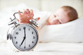 Alarm clock and sleeping young woman Royalty Free Stock Photo