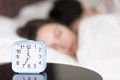 Alarm clock on table in front of sleeping young couple