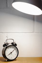 Alarm clock on table with lamp and blurred white brick Royalty Free Stock Photo
