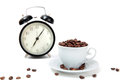 The alarm clock and white cup filled by coffee beans Royalty Free Stock Photo