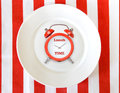 Alarm clock on white plate.Lunch time concept background Royalty Free Stock Photo