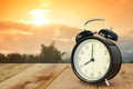 Alarm clock on wooden and beautiful sunrise background. Royalty Free Stock Photo