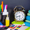 Alarm clocks and school supplies on the background Royalty Free Stock Image