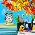 Alarm clocks and school supplies on the background of autumn leaves Royalty Free Stock Photos