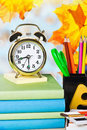 Alarm clocks and school supplies on the background of autumn leaves Stock Images