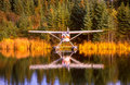 Alaska float plane moored at dock amid foliage reflections two planes in the water of the planes and colorful yellow of fall trees Stock Photos
