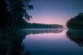 Alberi che riflettono nella superficie regolare dell acqua all alba Fotografia Stock
