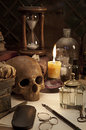 Alchemy still life with skull and burning candle Stock Photography