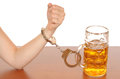 Alcohol abuse glas of beer with handcuffs as symbol for Royalty Free Stock Photos
