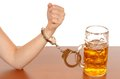 Alcohol abuse glas of beer with handcuffs as symbol for Royalty Free Stock Photography