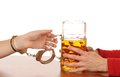 Alcohol abuse glas of beer with handcuffs as symbol for Stock Image