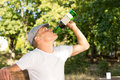 Alcohol abuser drinking from a bottle of wine male white sitting on bench in the park in warm summer day Stock Photo