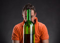 Alcohol addict looks at the bottle Royalty Free Stock Image