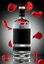 An alcohol romance a photo of luxury bottle with falling rose leaves Royalty Free Stock Photo