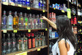 Alcohol sale of liquor act ashdod isr july young woman in a store on july consumed by humans since prehistoric times for hygienic Royalty Free Stock Photo