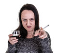 Alcoholic aggressive woman pointing while drinking red wine and smoking Royalty Free Stock Photography