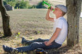 Alcoholic drinking alone in the countryside sitting on ground with his back against a tree gulping spirits from a bottle Stock Photo