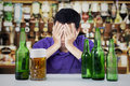 Alcoholic man in a bar sad with beer bottles and glass on the table Stock Photography