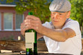 Alcoholic man feeling dizzy sitting at a table outdoors holding bottle of wine Stock Photos