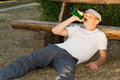 Alcoholic relaxing in a park with his liquor lying on the ground bottle of gulping down the contents Royalty Free Stock Photos