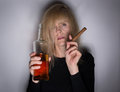 Alcoholic woman with cigar and whiskey disease concept bottle shadows Stock Image