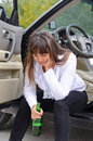Alcoholic woman driver stopping for a drink of bear from bottle sitting sill open door of her car with her head resting hand Stock Photos