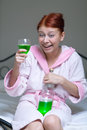 Alcoholic woman drunk with a bottle green cocktail Stock Image