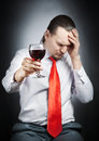 Alcoholism sick man holding the glass of red wine at black background Royalty Free Stock Photography