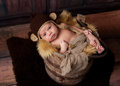 Alert newborn baby boy wearing a monkey hat looking at the camera he is crocheted and lying in an antique wooden well bucket shot Royalty Free Stock Photos