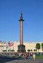 Alexander column on palace square covered with natural lawn of green grass and trees on a sunny day on the background of flags in Royalty Free Stock Images