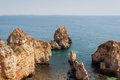 Algarve coast portugal rocks in the shoreline and blue water summer day Royalty Free Stock Images