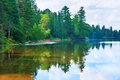 Algonquin lake tranquil scene of in ontario canada with trees and two red kayaks Royalty Free Stock Photos