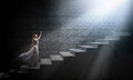 Alice in wonderland young woman white long dress stepping up the staircase Royalty Free Stock Image