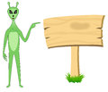 Alien pointing towards sign board a green empty wooden Stock Images