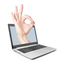 All perfectly the hand pops out of the laptop concept idea Stock Photos