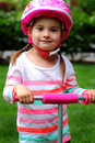 All ready to go a closeup of a sweet prissy little toddler girl with pigtails wearing a pink helmet standing on a pink scooter Stock Photography