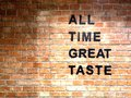 ALL TIME GREAT TASTE banner lettering on red, old orange brick wall background. Space for copy, text Royalty Free Stock Photo