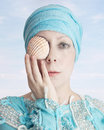 Allegory of sea woman in a powder blue dress wearing a turban she is holding a pale seashell in front her eyes as a symbol and Royalty Free Stock Image