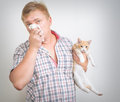 Allergic to animals man holding a cat is Royalty Free Stock Photos