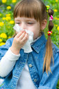 Allergy little girl is blowing her nose while sitting on green meadow Stock Photography