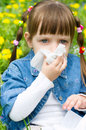 Allergy little girl is blowing her nose while sitting on green meadow Stock Images